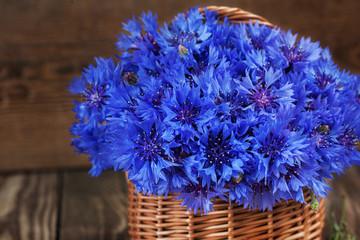 A bunch of beautiful summer flower of Cornflower in the basket.