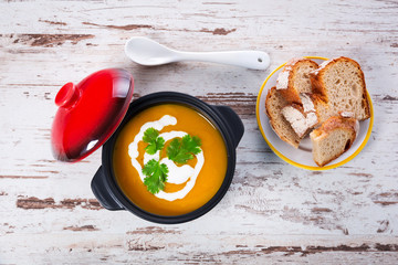 Pumpkin soup with cream in ceramic pot