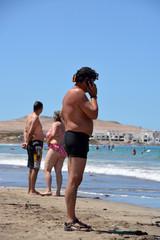 hombre hablando por telefono en la playa