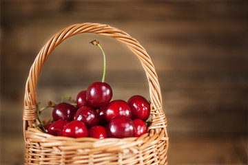 closeup  Ripe Sweet Cherry in the Basket  on  Wooden background