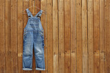 Pair of denim dungarees hanging against wooden wall.