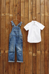 Dungarees and white shirt hanging against wooden background.