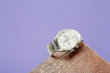 Luxury men's watch against colored background .