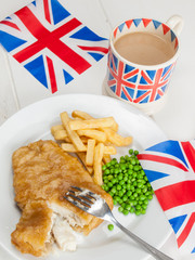 fish and chips with a cup of tea  in a union jack mug and britis
