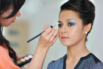 Pretty young woman applying makeup by makeup artist