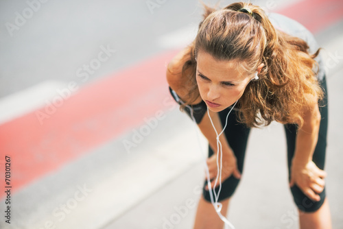 Poster Portrait of tired fitness young woman outdoors in the city