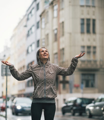 Portrait of happy fitness young woman catching rain drops