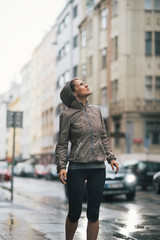 Fitness young woman exposed to rain while jogging outdoors