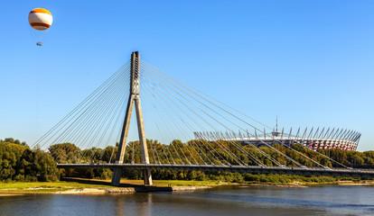Bridge, hot-air balloon and stadium over Vistula river in Warsaw