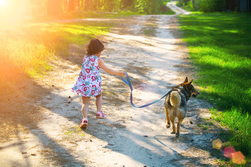Little girl with dog running on the road to the sun