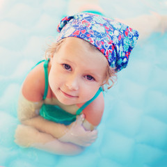 Smiling little girl in the swimming pool at summer