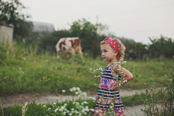 Smiling little girl in colorful dress on the summer field