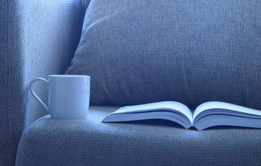 Open book with a cup of cofee on  bed