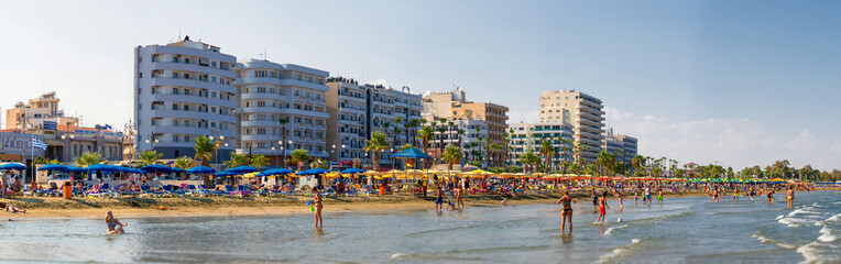 LARNACA, CYPRUS - 20 AUGUST 2014: People on the sunny beach of L