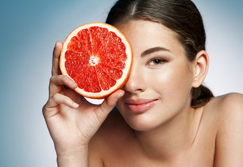 Glossy girl with grapefruit cut in half fruit in hand