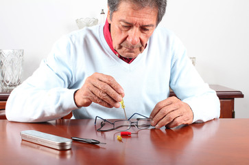 Senior man repairing glasses