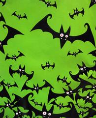 A flock of Halloween bats on a green background.