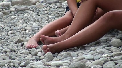 Legs of two girls sitting on a pebble beach.