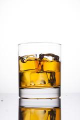 Whisky splashing in glass on a white background