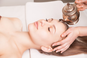 Woman enjoying Ayurveda oil head massage in spa