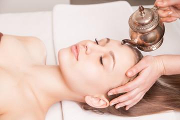 Woman enjoying Ayurveda oil head massage in spa