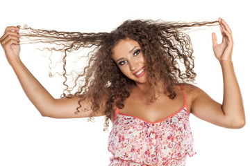 happy young woman holding her curly hair