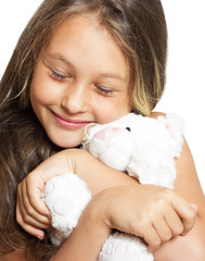 little girl tenderly embraces plush toy