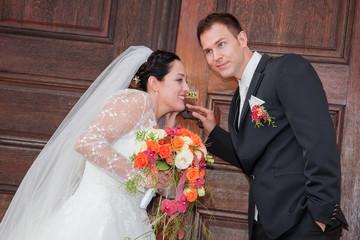 Brautpaar lauscht an Kirchentor ob die Gäste schon da sind