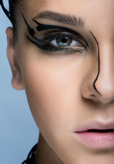 Close-up shot of young woman face with futuristic  makeup