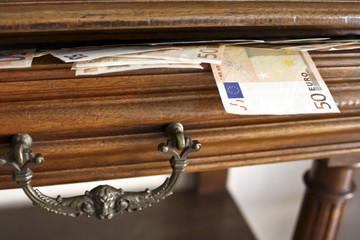 Billetes de 50 euros saliendo de un cajón