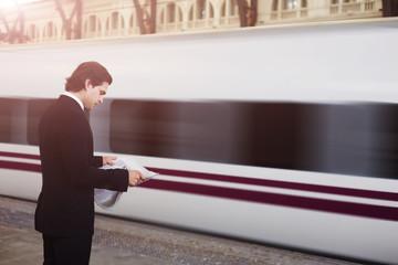 Handsome businessman stand on train railway station