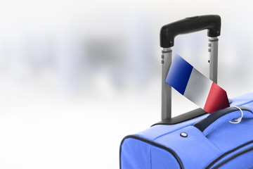 Destination France. Blue suitcase with flag.
