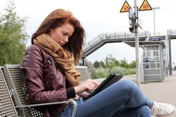 junge Frau überbrückt Wartezeit mit Tablet