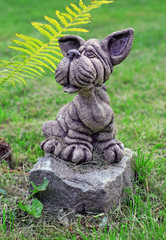Garden stone statue of dog on the lawn