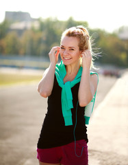 Young sporty woman in the morning with headphones on treadmill