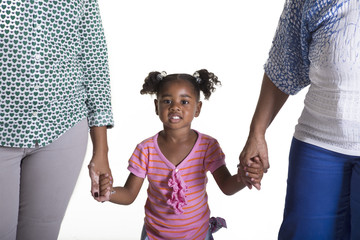 Young preschool child holding hands with 2 adults