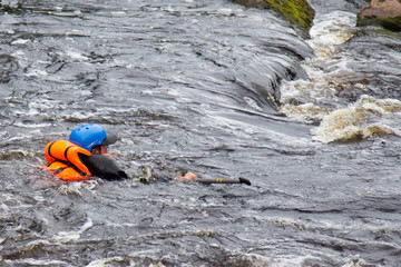 people in life jackets drowning in a turbulent river