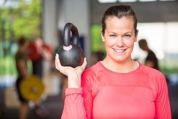 Fit Woman Lifting Kettlebell At Gym
