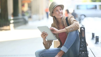 Trendy girl using tablet sitting on bench in town