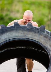 Determined Athlete Doing Tire-Flip Exercise