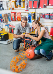 Saleswoman Assisting Customer In Using Air Compressor