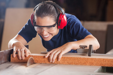 Female Carpenter Cutting Wood With Tablesaw