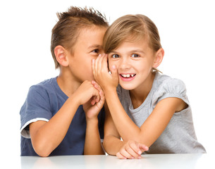 Little girl and boy are whispering in ear