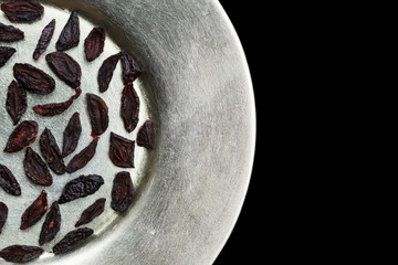 Dried zwetschke plums on silver plate still life.