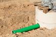 Ein grünes Abwasserrohr aus Kunststoff an einem Kanalschacht