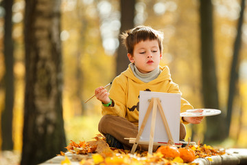 Cute little boy painting in golden autumn park