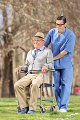 Male nurse pushing a senior in wheelchair on a sunny day