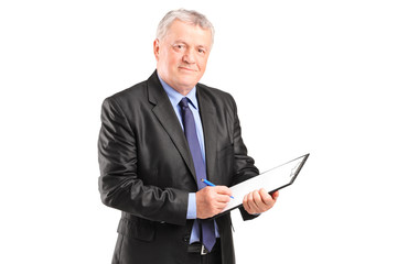 Mature businessman taking notes on piece of paper