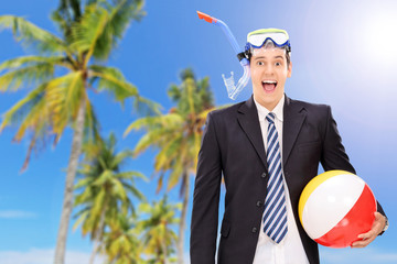 Man standing on beach with snorkel and ball