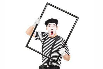 Mime artist holding a big picture frame
